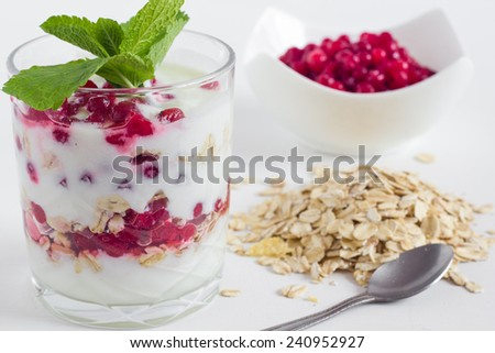Layered yogurt with red currants and oats on a white table. Healthy breakfast idea. - stock photo
