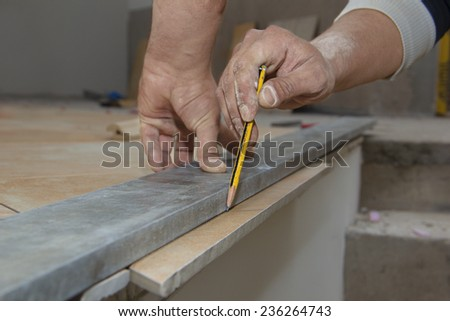 Laying ceramic floor tiles - man hands marking tile to be cut, closeup - stock photo