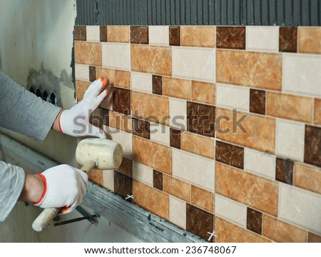 Laying Ceramic Tiles. Tiler knocking on the tiles with a rubber mallet - stock photo