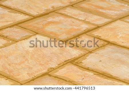 Laying concrete outdoor tiles, sandstone colored paving on the terrace with brown not dry joints - stock photo