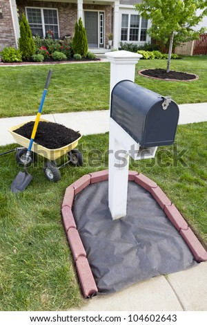 Laying mulch around the mailbox and placing edger bricks. - stock photo