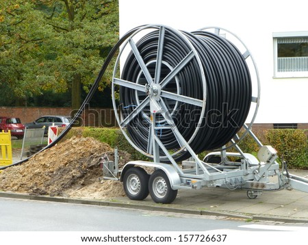 Laying of fiber optic cable in Hanover, Germany.  Glass fibers are employed as fiber optic cable for data transmission and for flexible transport of light. - stock photo