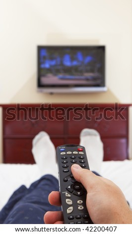 laying on a bed and watching tv - stock photo