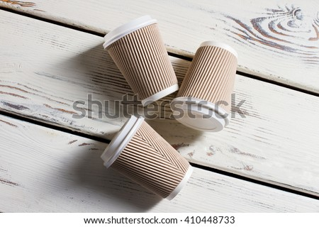 Laying ripple paper cups. Hot drink cups with lids. Disposable cups on white table. Running out of coffee. - stock photo