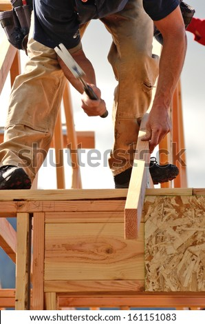 Layout and installation of roof rafters on a new commercial residential construction project by framing contractors - stock photo