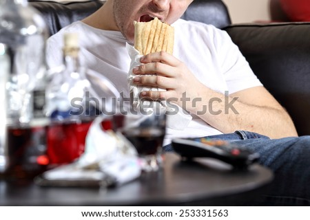 Lazy and fat man eats a kebab on the couch - stock photo