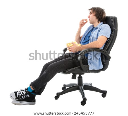 Lazy man sitting in armchair eating pop corn, isolated at white background - stock photo
