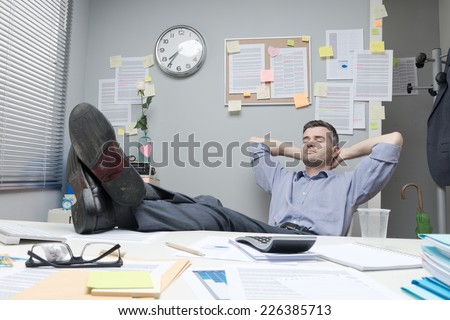 Lazy office worker feet up relaxing in his small office. - stock photo
