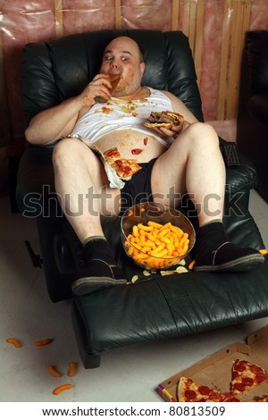 Lazy overweight male sitting on a couch watching television.  Harsh lighting from television with slow shutter speed to create TV watching atmosphere. Selective focus on the eyes. - stock photo