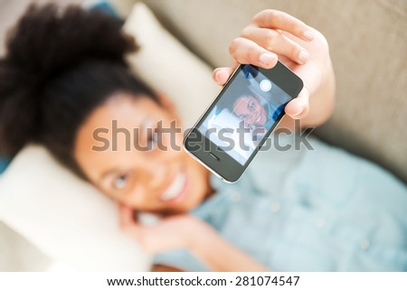 Lazy selfie. Top view of attractive young African woman in headphones listening to the music and smiling while lying on the couch at home - stock photo