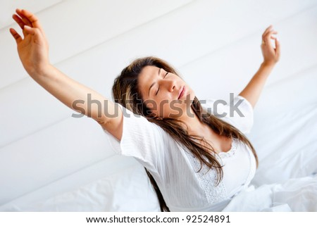 Lazy woman in bed waking up and yawning - stock photo