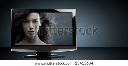 LCD television set on reflective table - stock photo