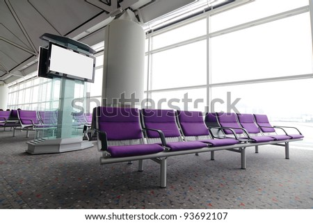 LCD TV and row of purple chair at airport - stock photo