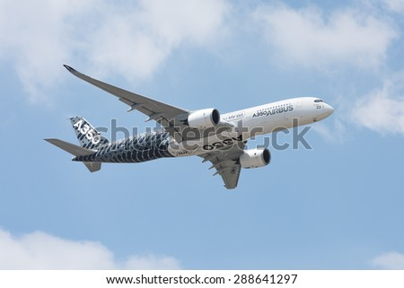 LE BOURGET, FRANCE - JUNE 16, 2015 : Airbus A350 XWB flying at he Paris air show. This plane is a mid-size long range aircraft family and the World's most modern and efficient aircraft. - stock photo