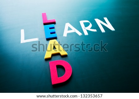 Lead and learn, conceptual words on blackboard - stock photo