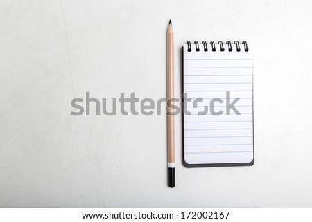 Lead pencil and notebook on white table - stock photo