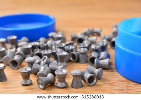 Leaden air rifle shots and blue plastic box on wooden background, close up - stock photo