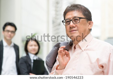 Leader and team member. Portrait of 60s Asian Chinese CEO boss smiling. Senior male businessman and staffs, real modern office building as background. - stock photo