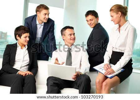 Leader of business team pointing at the screen of his laptop, his colleagues looking at him - stock photo