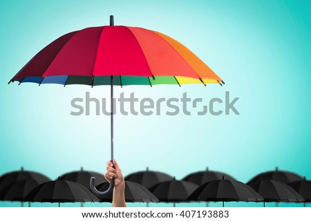 Leader person's hand holding rainbow umbrella distinctive unique among black color others on blue mint vintage sky background: Life-health Insurance protection, Business financial leadership concept  - stock photo