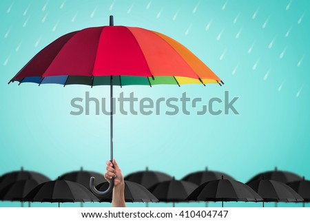 Leader person's hand holding rainbow umbrella distinctive unique among black color others on blue mint rainy sky background: Life health Insurance protection, Business financial leadership concept  - stock photo