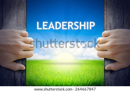 Leadership concept. Hand opening an old wooden door and found a texts floating over green field and bright blue Sky Sunrise. - stock photo