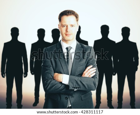 Leadership concept with handsome caucasian businessman in front of businesspeople silhouettes - stock photo