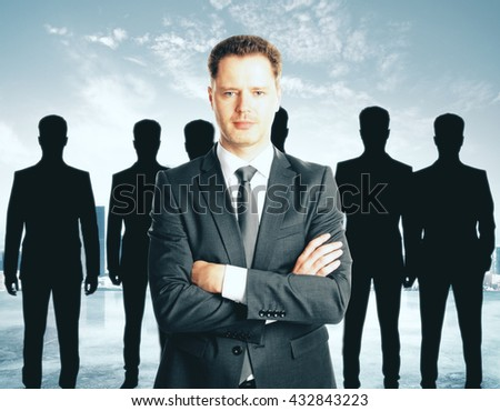 Leadership concept with handsome caucasian businessman in front of businesspeople silhouettes on abstract background - stock photo