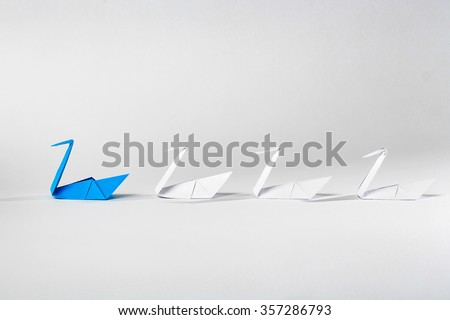 Leadership concept with origami paper bird leading among white. - stock photo