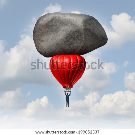 Leadership power and business challenges concept as a businessman piloting a red hot air balloon with a huge heavy rock slowing the rise as an obstacle to career and financial success. - stock photo