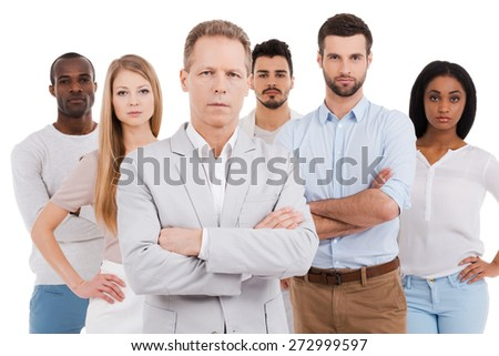 Leading his team to success. Confident mature man in smart casual wear keeping arms crossed and looking at camera while group of young people standing behind him and against white background  - stock photo