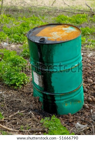 Leaking oil barrel left on a field - stock photo