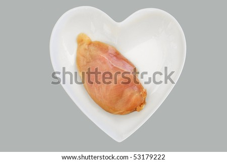 lean corn fed chicken breast on heart shaped dish - stock photo
