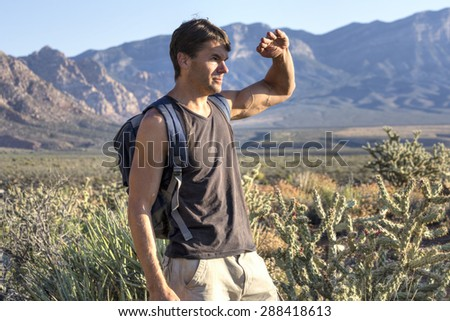 Lean muscular Caucasian man hiking in desert shields eyes from intense morning sunlight - stock photo