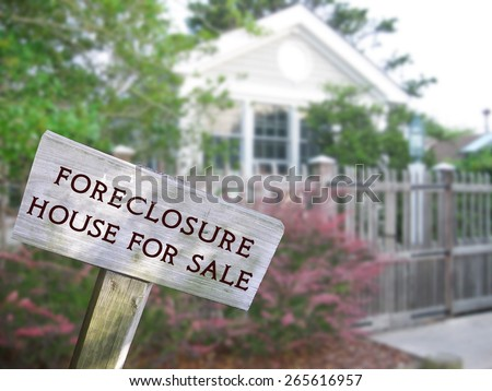 Leaning home for sale real estate and foreclosure sign in front of a modern single family home.  - stock photo