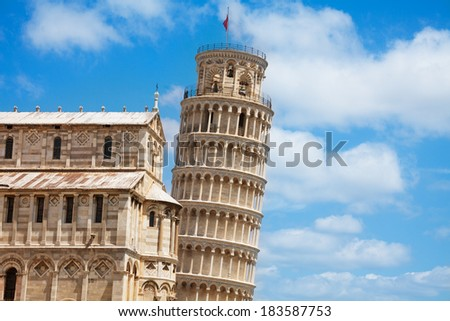 Leaning Pisa tower and part of cathedral with sky clouds as background - stock photo