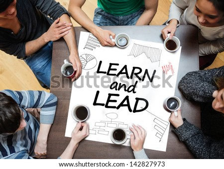 Learn and lead written on a poster with drawings of charts during a brainstorm - stock photo