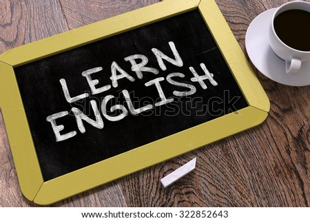Learn English. Motivational Quote Handwritten on Yellow Chalkboard. Business Concept. Composition with Chalkboard and Cup of Coffee. Top View Image. - stock photo