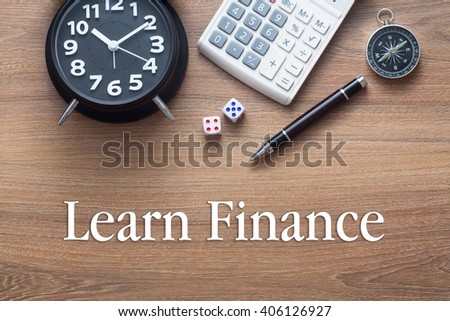 Learn Finance written on wooden table with clock,dice,calculator pen and compass - stock photo