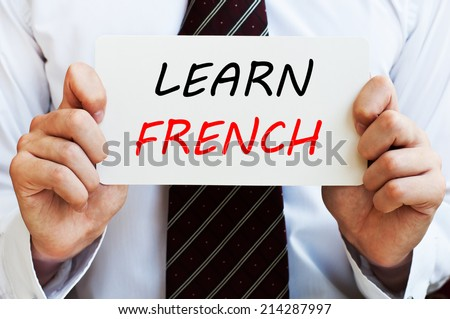 Learn French - man wearing a shirt and a tie holding a signboard with a text on it. Education concept. - stock photo