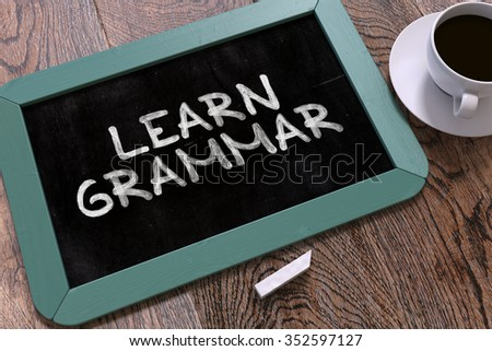 Learn Grammar - Blue Chalkboard with Hand Drawn Text and White Cup of Coffee on Wooden Table. Top View. - stock photo