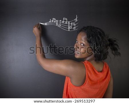 Learn music South African or African American woman teacher or student with chalk music notes blackboard background - stock photo