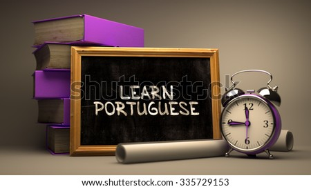 Learn Portuguese - Chalkboard with Hand Drawn Inspirational Quote, Stack of Books, Alarm Clock and Rolls of Paper on Blurred Background. Toned Image. - stock photo