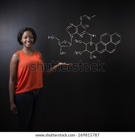 Learn science or chemistry formula confident beautiful South African or African American woman teacher or student chalk blackboard background - stock photo