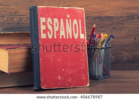 learn spanish concept. book on a wooden background - stock photo