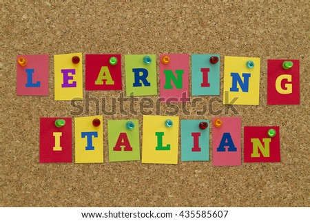 Learning Italian word written on colorful notes pinned on cork board. - stock photo