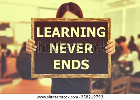 LEARNING NEVER ENDS message on the blackboard wooden frame on hand woman with blurred student study learning in classroom. Vintage or retro tone. - stock photo
