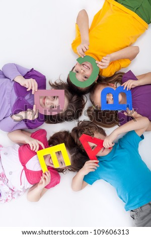 Learning through playing concept - kids with large alphabet letters - stock photo