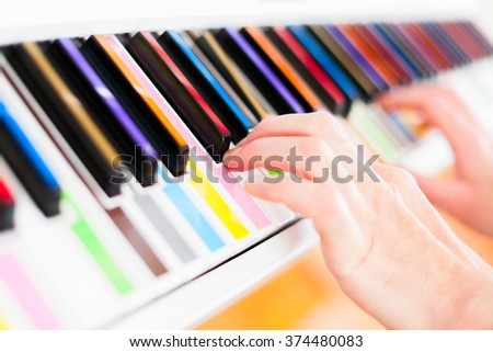 Learning to Play white piano with multi colore keys - stock photo