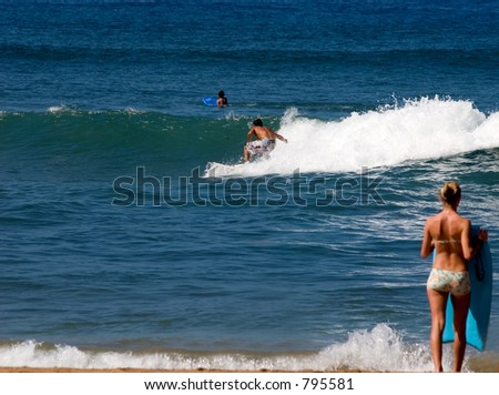 Learning to surf in Maui with girl on Beach watching. Focus is on the surfer - stock photo